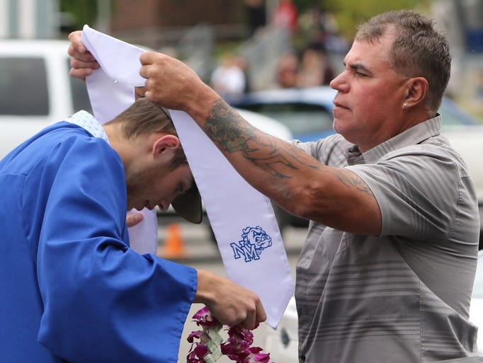 Mack Coldiron helps his son, Tanner, with his graduation