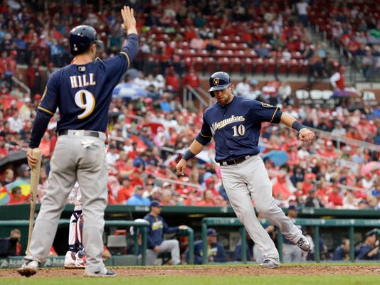 Milwaukee Brewers' Kirk Nieuwenhuis, right, scores as teammate Aaron Hill celebrates on a two-run double by Ramon Flores during the fourth inning of a baseball game against the St. Louis Cardinals, Sunday, July 3, 2016, in St. Louis. (AP Photo/Jeff Roberson)