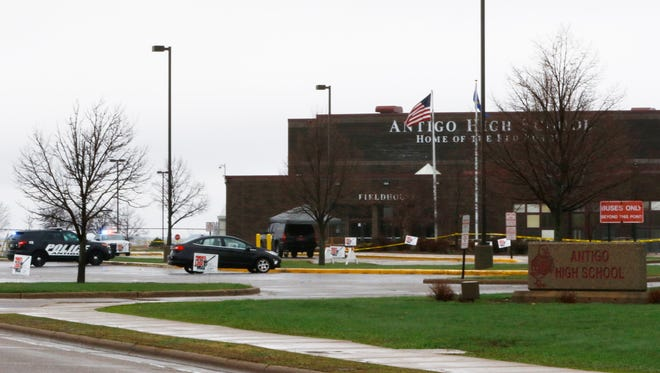 Yellow tape surrounds the parking lot outside Antigo High School on Sunday during the investigation of a post-prom shooting Saturday night.