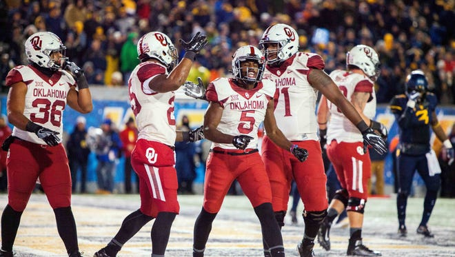 Oklahoma Sooners players celebrate after scoring a second quarter touchdown.