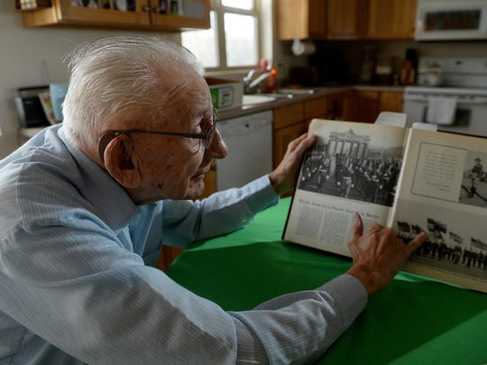 Bud Olson, a World War II veteran, points to himself in a commemorative book about the American occupation of Berlin at the close of World War II. He went house-to-house in the American sector looking for war material.