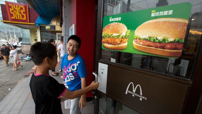 Boys open the door to a McDonald's restaurant in Beijing in 2014. On Tuesday, Aug. 8, 2017, McDonald's said it plans to nearly double the number of restaurants in China in the next five years, eventually surpassing Japan as the hamburger chain's second-biggest market outside the United States. The company expects to have 4,500 restaurants in China by 2022, up from 2,500.