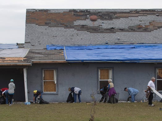 Volunteers gather Thursday to clean the yard of a home