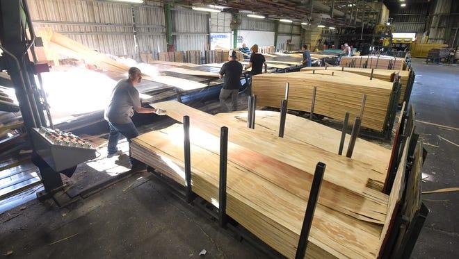 A crew stacks veneer at in 2016 at Freres Lumber Co. in Lyons.