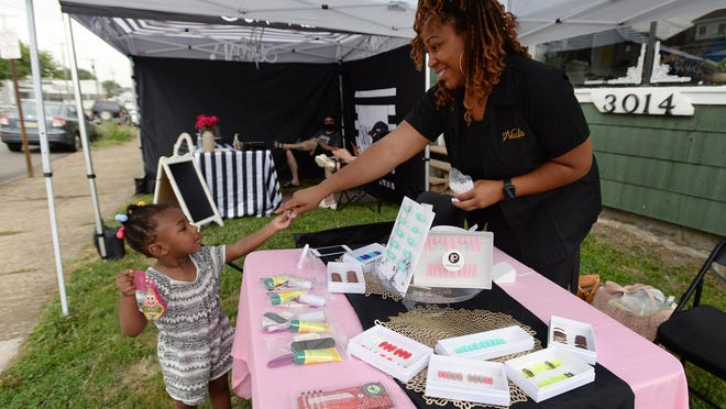 Deanna Dias, of Erie, owner of Press On Posse, gets some help from her daughter Deena Dias, 2, while selling her nail products Saturday during the pop-up shop event at She Vintage in Erie.