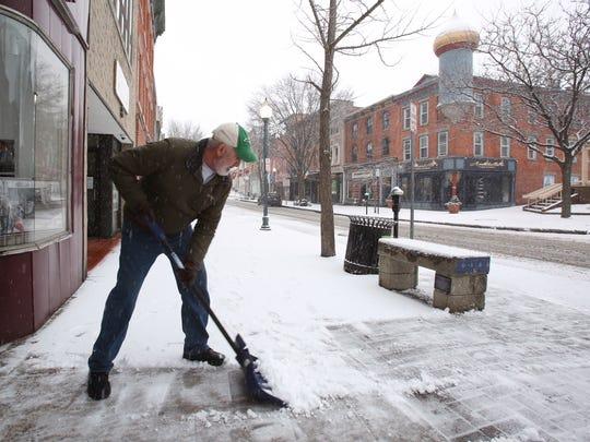 Charlie Kavana shovels the snow outside the Robert