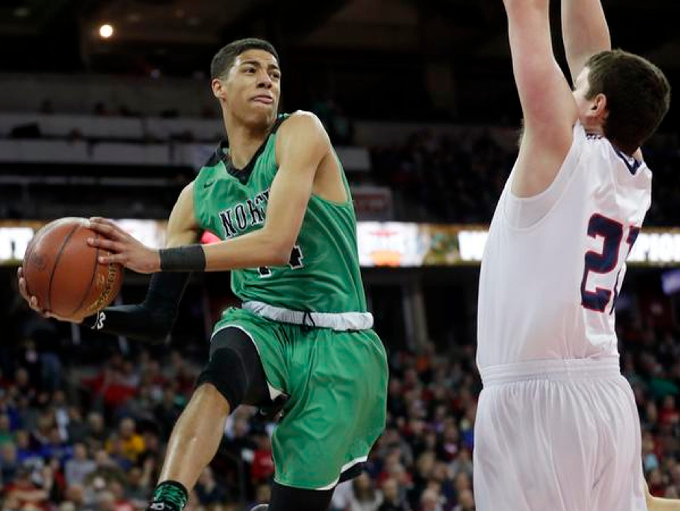 Oshkosh North's Tyrese Haliburton (14) looks for an open teammate in midair against Brookfield East in the Division 1 state championship game on Saturday, March 17, 2018, at the Kohl Center in Madison. Haliburton's Spartans won the state title.