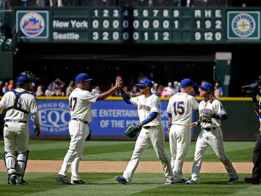 The Mariners celebrate after their 9-1 win over the