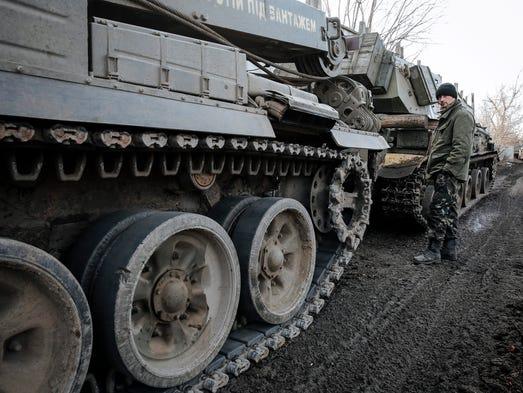 A Ukrainian serviceman stands next to tanks during