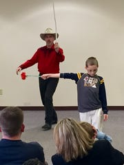 Chris Camp slashes a fake flower out of a volunteer's hand Sunday, Feb. 21, at the Tippecanoe County Public Library in Downtown Lafayette.