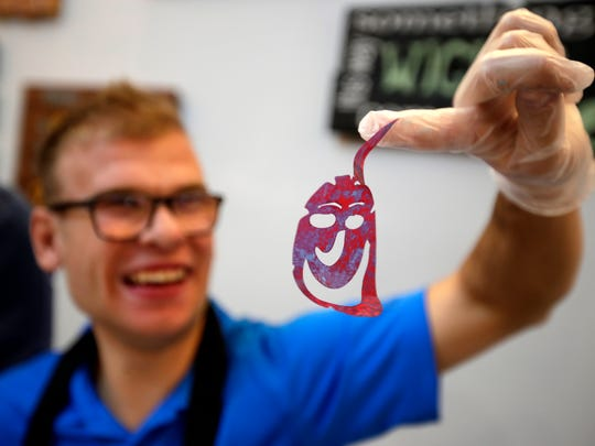 Henry Weidert laughs on Friday as a cutout smiley face stencil is stuck to his finger while working on an art project with the Fox Valley Metro Police Department at Crafty Wood Maker Studio in Appleton.