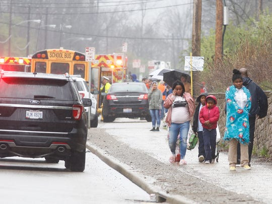 A family leaves the scene of a Winton Road crash that involved a school bus with students from Pleasant Hill Academy Monday.