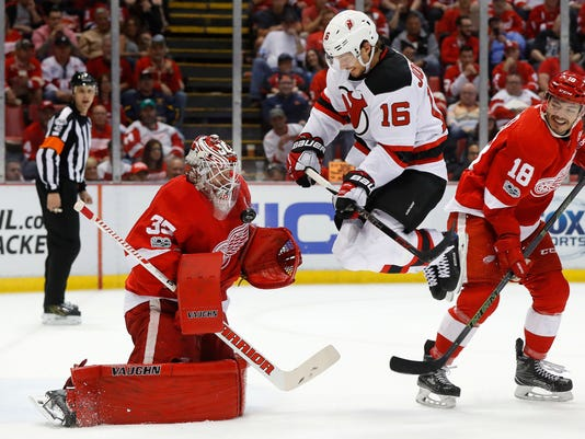New Jersey Devils center Jacob Josefson (16) jumps as Detroit Red Wings goalie Jimmy Howard (35) stops a shot during the first period of the final NHL hockey game at Joe Louis Arena, Sunday, April 9, 2017, in Detroit. (AP Photo/Paul Sancya)