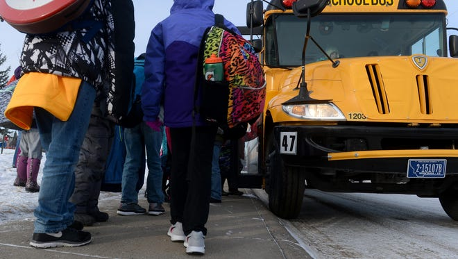 Meadow Lark Elementary School students load onto their school bus on Wednesday after school.