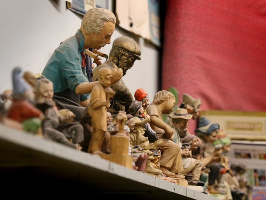 Cobbler statues fill a shelf at John's Shoe Service