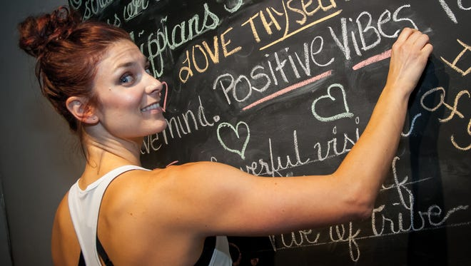 "Total Body Bar owner Tierney Jeffers writes an empowering message on her studio's ""Positivity Board."""