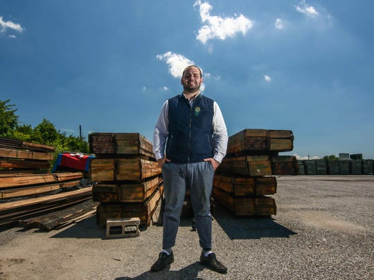 Branch Manager Sam Rogers stands near repurposed wood at Repurposed Materials in Wilmington on Wednesday, June 29, 2016.