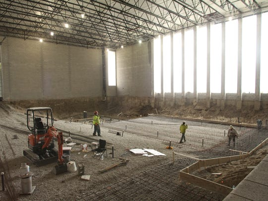 Workmen place steel rebar reinforcing along the sloped pool floor prior to pouring of concrete at the Brighton High School facility.
