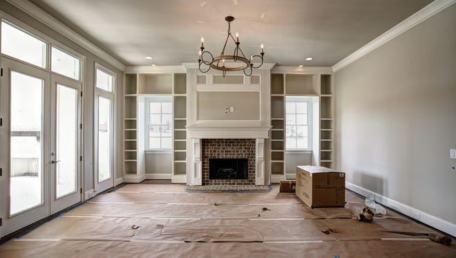 The star of this  gathering space is a large fireplace with brick surround, flanked by custom built-ins. Oversized crown molding and baseboards create a crisp symmetry with the masonry that surrounds the fireplace and mantle and complements the cool gray tones of the room. Open to the gourmet kitchen and allowing access to the stunning backyard covered porch, this room is a show stopper.