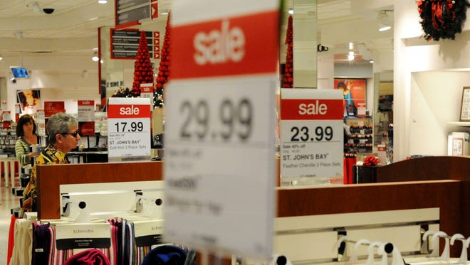 Sale signs and holiday decorations line the walls and racks of JCPenney at Acadiana Mall.