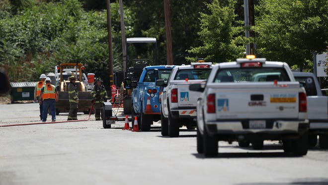 Crews from Pacific Gas & Electric and Anderson firefighters work to contain a gas leak Thursday on Veterans Lane in Anderson.