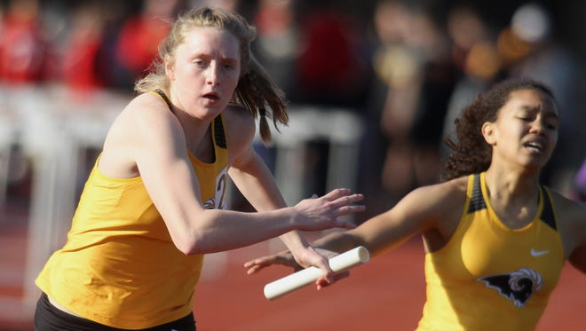 Southeast Polk's Grace Larkins takes the baton from Magda McGowan for the anchor leg of the 4x800-meter relay at the Simpson College High School Classic on March 26 in Indianola.