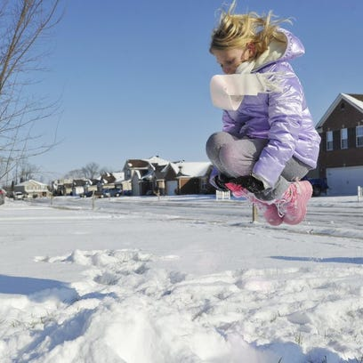 ERIN MCCRACKEN / COURIER & PRESS   Kayla Allen, 9, jumps into a pile of snow she made while playing with her siblings at their home in Newburgh while enjoying their snow day.