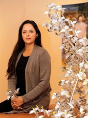 "El Paso artist Margarita Cabrera sits by her ""Uplift"" display at the University of Texas at El Paso Centennial Museum. The sculpture is a representation of birds achieving flight and therefore freedom, according to the artist."