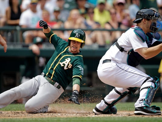 Oakland Athletics' Jed Lowrie, left, scores as Seattle Mariners catcher Mike Zunino waits for the ball in the fifth inning of a baseball game Sunday, July 13, 2014, in Seattle. (AP Photo/Elaine Thompson)