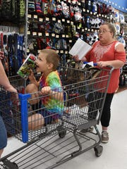 Conner Carroll, 6, gets help shopping at Walmart from