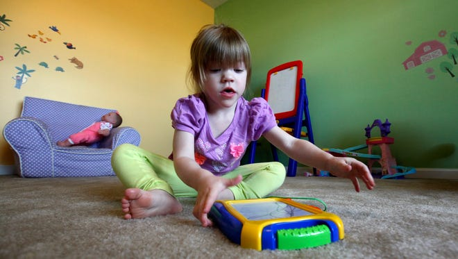 Addyson Benton, 2, plays inside her Liberty Township home March 18. Addyson, who has epilepsy, has hundreds of seizures every day and is on a Colorado waiting list for a special strain of medical marijuana.