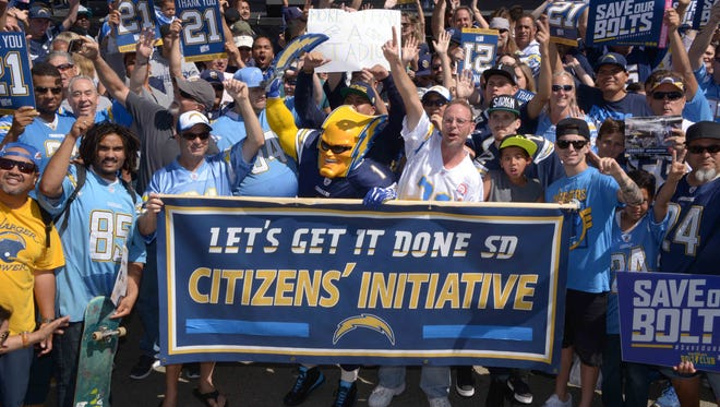 San Diego Chargers fan Dan Jauregui, aka Boltman, poses with Charger fans during a rally to gather signatures for citizen's initiative for a downtown stadium and convention center.