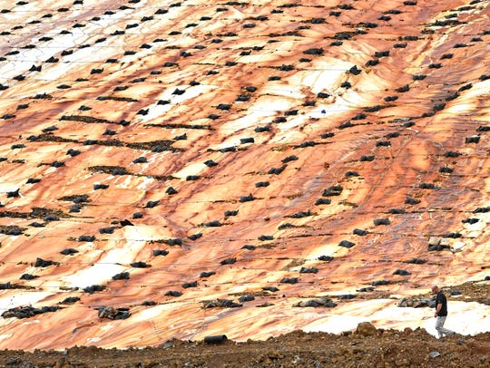 A worker passes by a stained covering of the county landfill that county officials say is leaching toxins on April 19, 2017.
