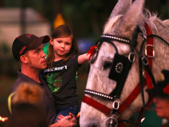 Riley Thompkins, 5, and her father Brendan take a closer look at Moonshine the Mule of Charlene's Classic Carriages during Holiday in the Park, Tuesday, Dec. 6, at Riverside Park.