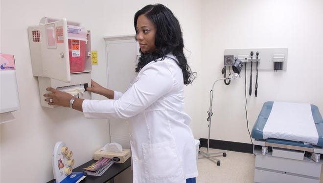 University of Mississippi Medical Center nurse practitioner CeNedra Lee puts finishing touches on installation of equipment at the new Lanier High School Teen Wellness Clinic.