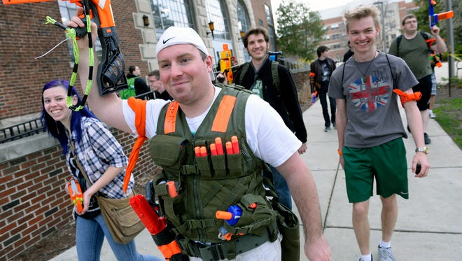 Evan Filipiak salutes with his Nerf gun as he and hundreds of others take part in a Spartans vs. Zombies game Tuesday on campus in East Lansing.
