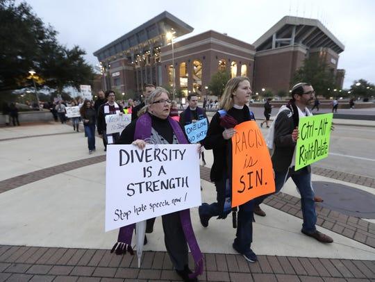 Demonstrators walks past Kyle Field toward the venue