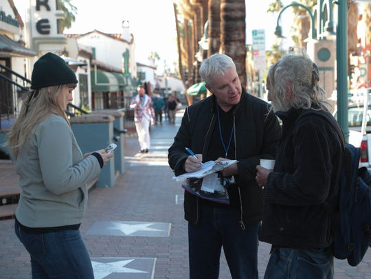 James Williamson, center, talks to a homeless man in