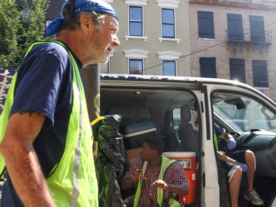 Workers with the Jobs Van Program take a water break on Wednesday, July 11, 2018 in Over-The-Rhine. The new program run by City Gospel Mission pays homeless and panhandlers $9 an hour to pickup trash in an effort to reduce panhandling.