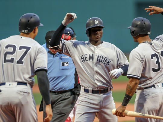 Aug 2, 2018; Boston, MA, USA; New York Yankees shortstop Didi Gregorius (18) celebrates with New York Yankees left fielder Giancarlo Stanton (27) and New York Yankees center fielder Aaron Hicks (31) after hitting a three run home run off of Boston Red Sox starting pitcher Brian Johnson (61) during the first inning at Fenway Park.