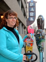 Joan Redeen of the Great Falls Business Improvement District with four painted parking meters in front of the 4th Street North parking structure on Monday morning.  Joan uses these meters as an example of a project she is working on to decorate decomissioned analogue meters that will be planted in front of the 4th street structure as an interactive art installation.  The money collected in the meters with help fund future art projects downtown.