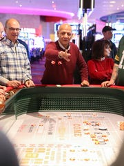 A guest rolls the dice on a craps table at the grand