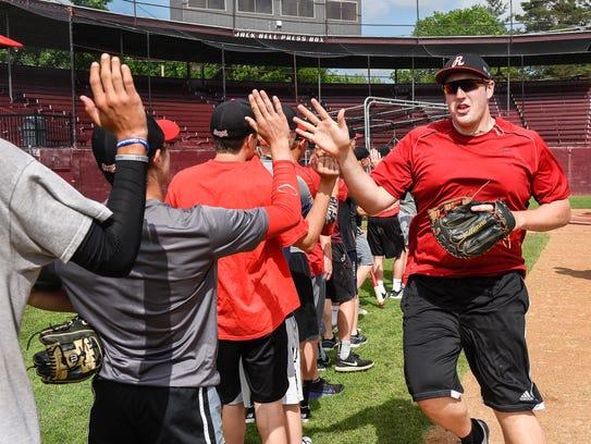 Rocori's Matthew Waletzko is greeted by  teammates