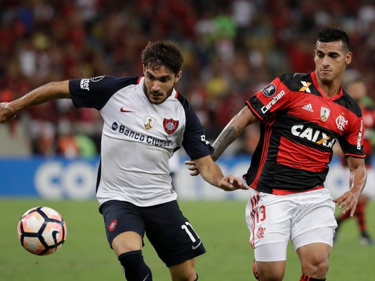Ezequiel Cerutti, of Argentina's San Lorenzo, left, fights for the ball with Miguel Trauco, of Brazil's Flamengo, during a Copa Libertadores soccer match at Maracana stadium in Rio de Janeiro, Brazil, Wednesday, March 8, 2017. (AP Photo/Felipe Dana)