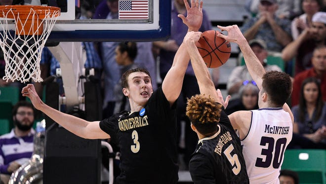 Northwestern guard Bryant McIntosh (30) is defended by Vanderbilt forward Luke Kornet (3) and guard Matthew Fisher-Davis (5) during the second half in the NCAA Tournament first-round game in Salt Lake City on March 16, 2017.