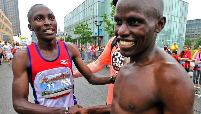 First place finisher Sammy Rotich, left, of West Des Moines, shook hands with Mathew Chesang, right, of Riley, Kansas, second place finisher, at the finish line at the Dam To Dam half marathon men's race in downtown Des Moines on Saturday morning May 31, 2014.