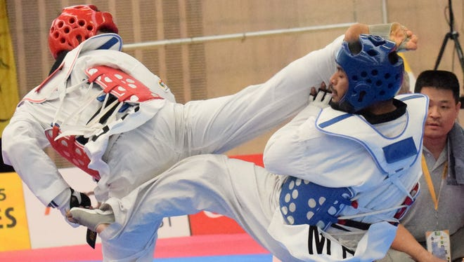 Guam national taekwondo team member Joseph Ho connects on a head kick during his competition July 17 at BSP Arena at the Pacific Games in Port Moresby, Papua New Guinea. The head kick gave Ho a lead for most of the match, but his opponent came back late in the match to win 7-5.