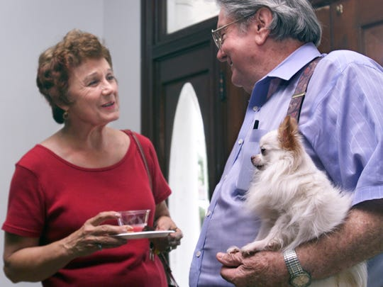 Verna Stone (left), a volunteer at the Art Museum of South Texas, and Corpus Christi artist Wesley Walberg with his longhaired Chihuahua named Mickey attend an opening reception for Barbara McDowell's art at the Galvan House at Heritage Park. Walberg died Wednesday, May 9, 2018.