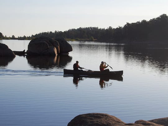 Canoeists paddle past granite boulders in Dowdy Lake in the early morning light in this August 2009 file photo.