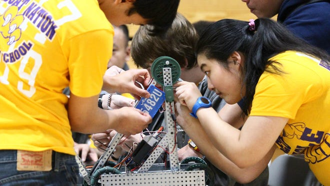 Izon Rai, left, and Rinda Shen of Redwood Academy in Ukiah work on their team's robot Saturday to get ready for the Starstruck Battle of the North VEX Robotics Competition at Shasta High School.
